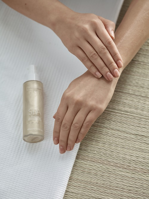 Hands next to a bottle of body highlighter.