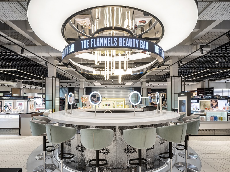 Flannels Beauty Bar- a circular table with high stools and mirrors.