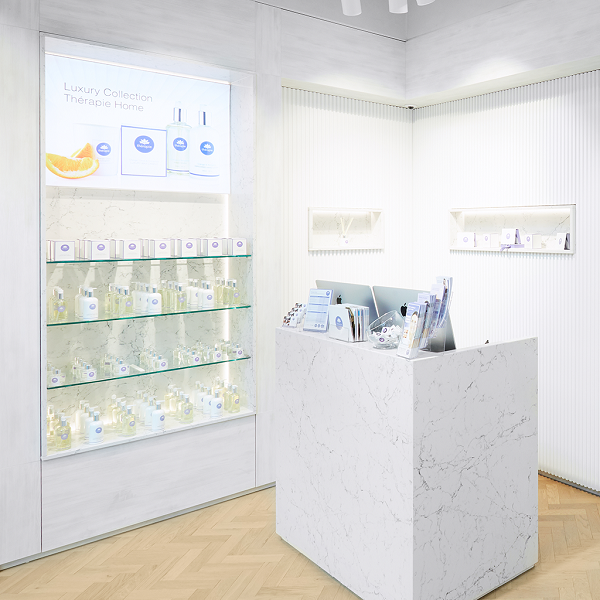Interior image of Therapie clinic with a desk and shelves with products on.