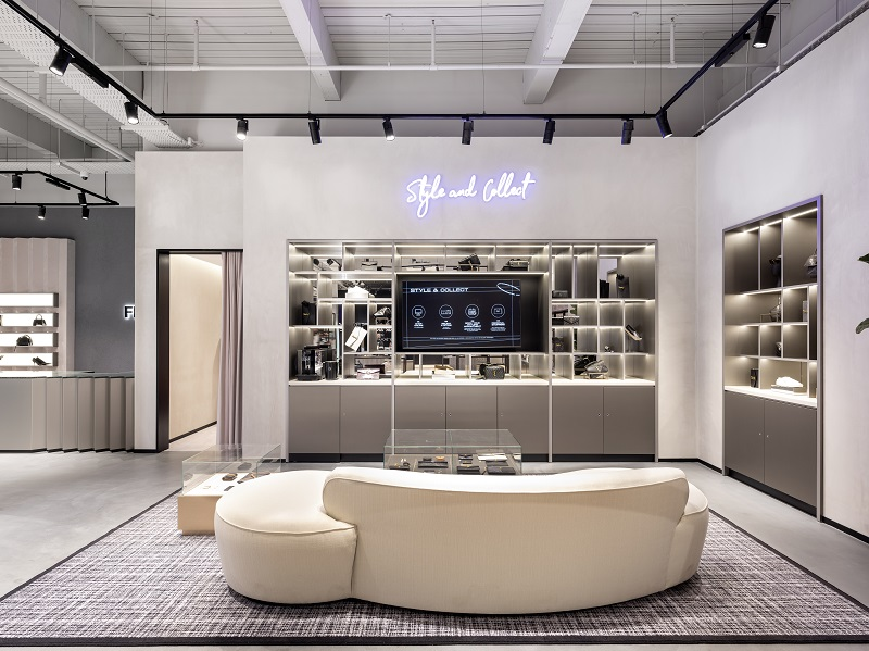 A section of Flannels store with a neon light saying 'style and collect' and a large modern sofa.