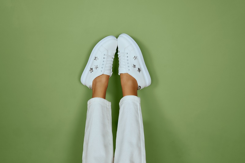 Legs wearing white trainers from Quiz.