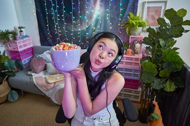 A girl wearing headphones and holding a bowl of snacks.