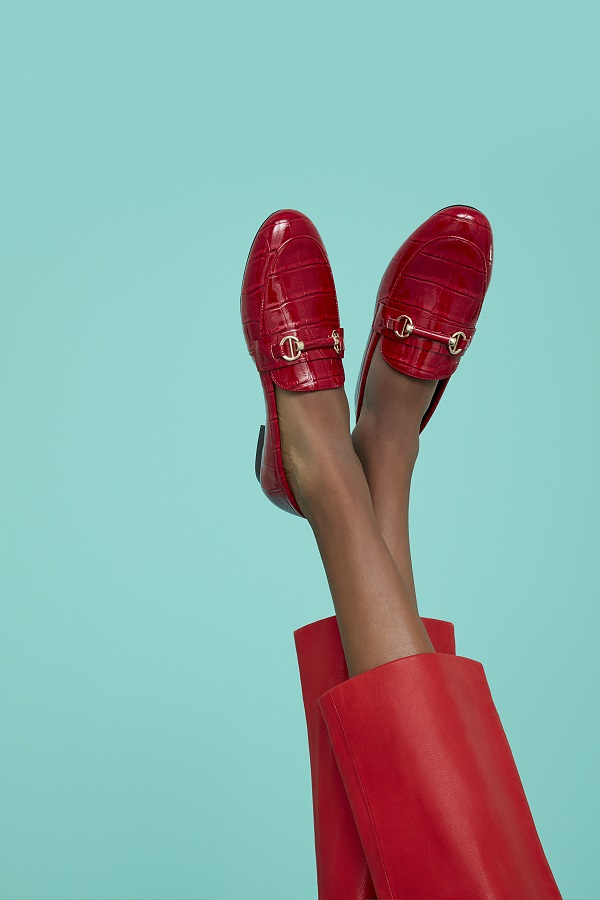 Some legs wearing red trousers and red loafers.