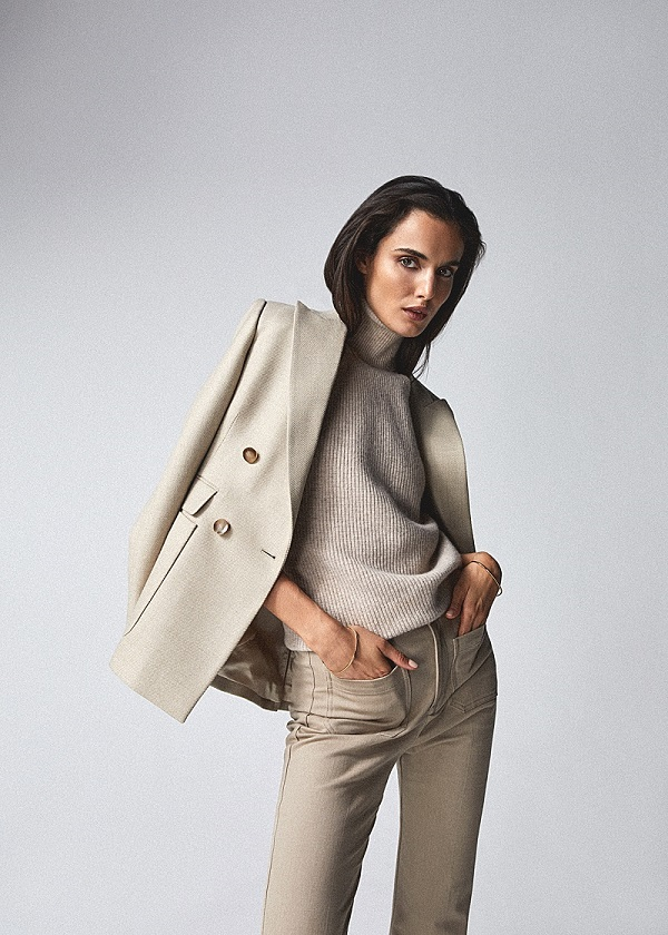 A woman wearing beige top trousers and blazer from Reiss