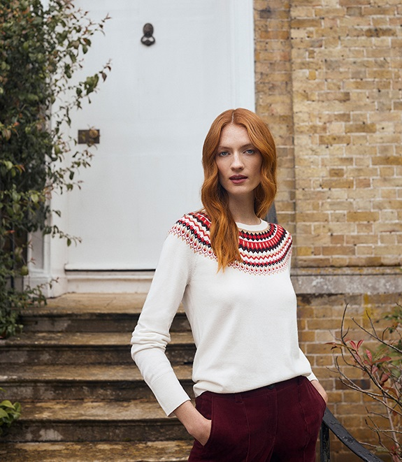 A model standing at the front of the house wearing a knitted jemper.