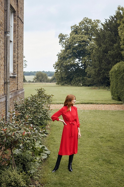 Woman in red Hobbs dress with black high boots in garden