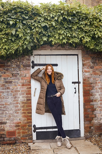 Woman stood outside a white door wearing Brown hobbs coat with black top, jeansand hiking boots