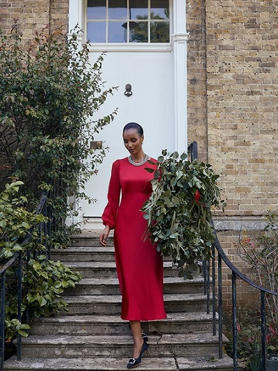 Women in red hobbs dress with black shoes carrying flowers
