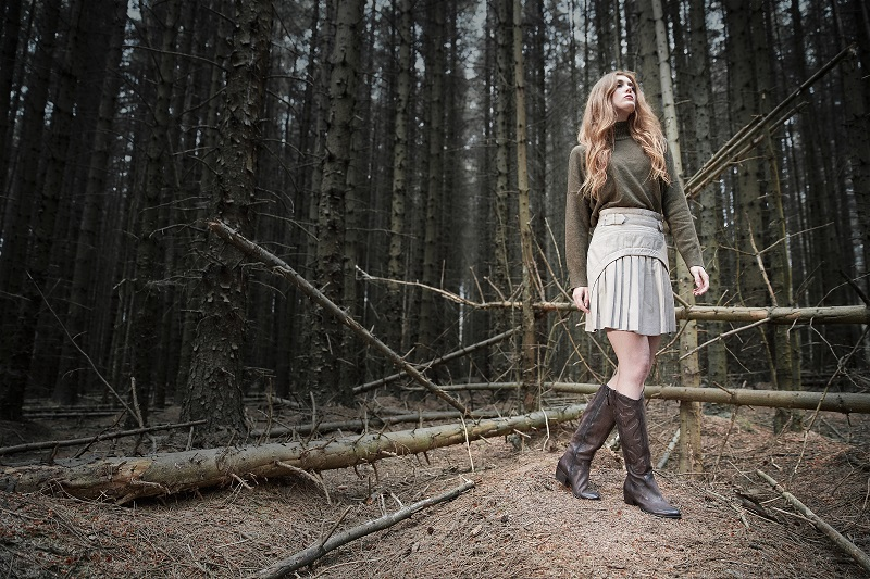 A model standing in a woods with brown cowboy boots on.