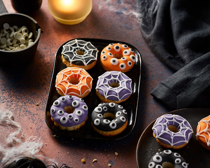 Colourful doughnuts decorated with icing in the shape of spiderwebs or eye balls.