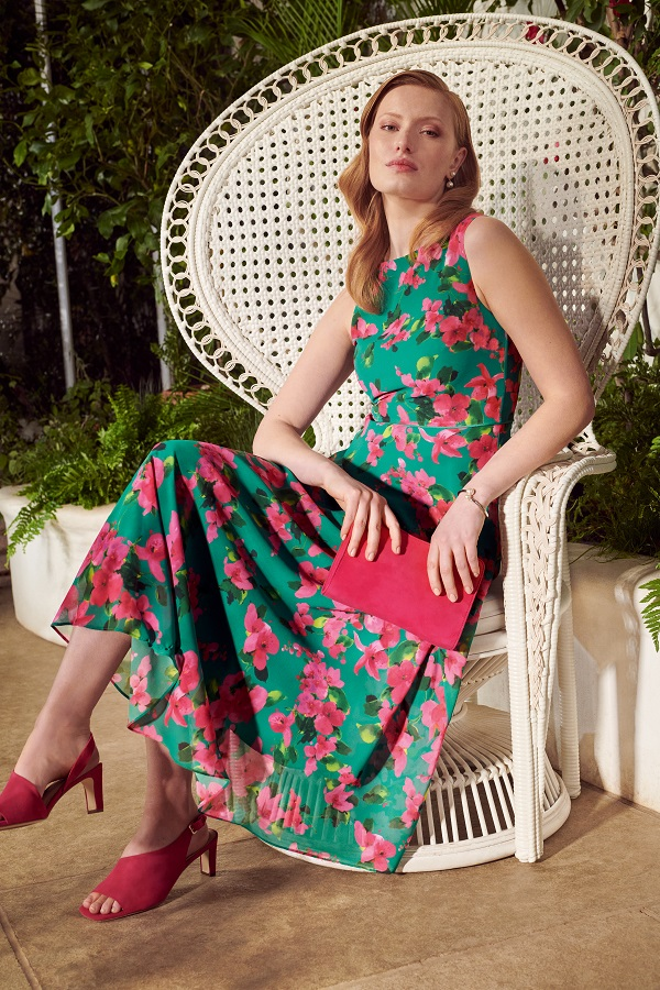 A woman sitting on a white chair and wearing a bright floral dress.