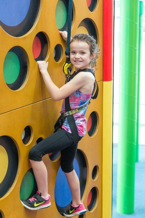 A young girl climbing a wall at Rock Up.