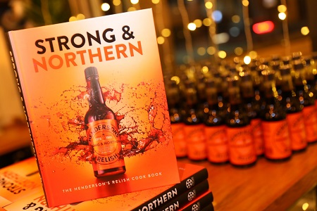 A book called strong and northern in front of bottles of henderson's relish.