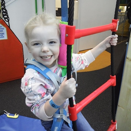 A young girl climbing a play ladder at Rock Up.