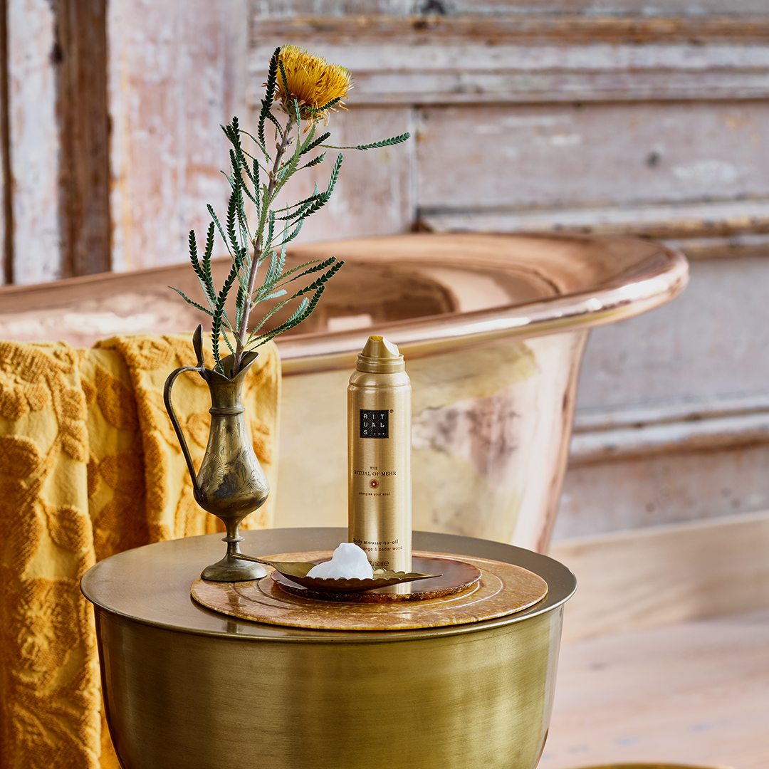a gold rituals mousse bottle on a table in a golden themed bathroom.