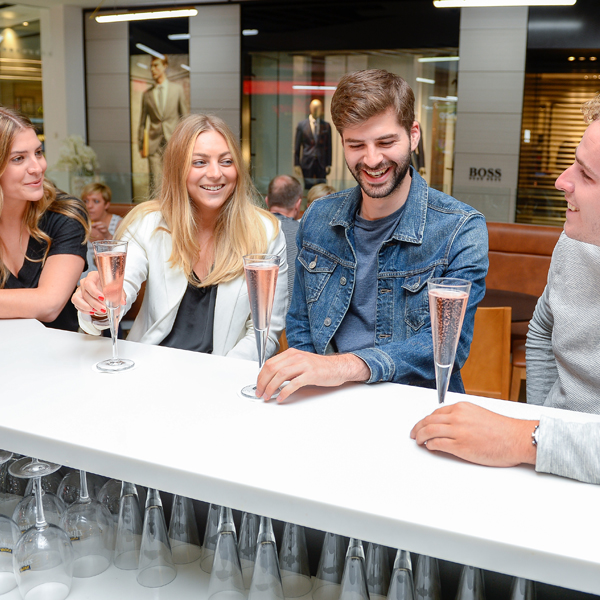 Four people drinking prosecco at a bar.