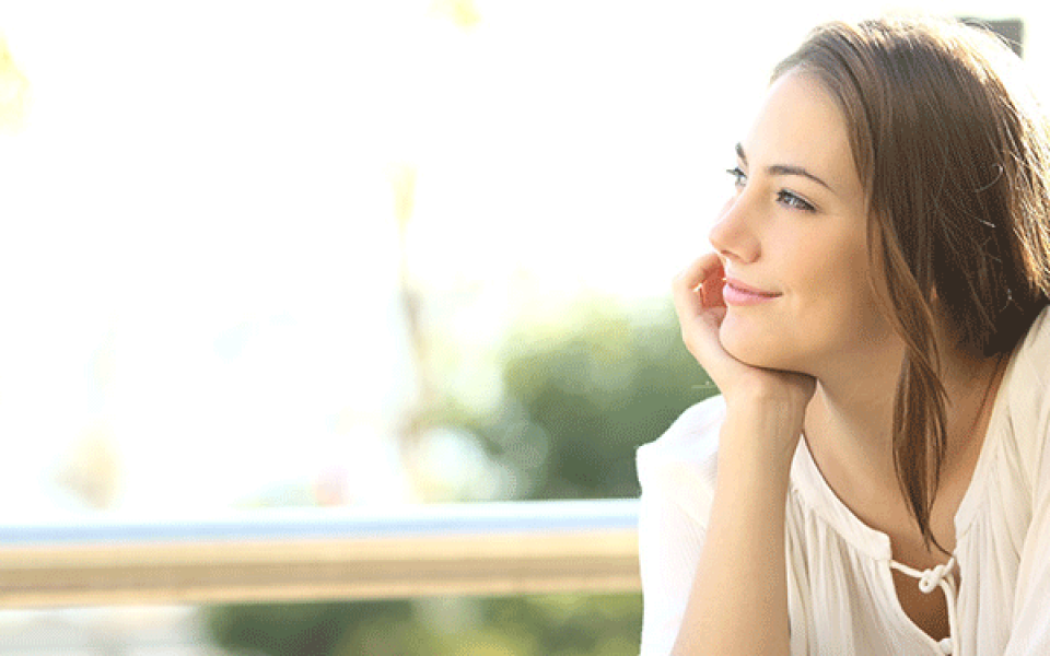 Woman in white top sat with resting her head on her hand looking into the distance