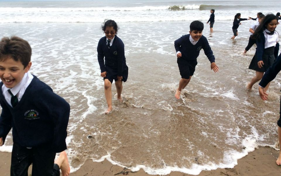 Tinsley Meadow Students at the seaside walking barefoot on the shore