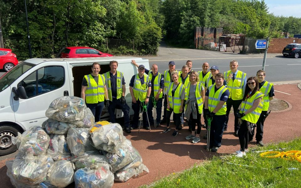 Team from Meadowhall in high vis jackets litter picking in the sunshine with a pile of bin bags of rubbish they have collected
