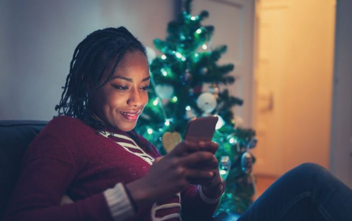 Woman in red jumper looking at phone with Christmas tree in the background