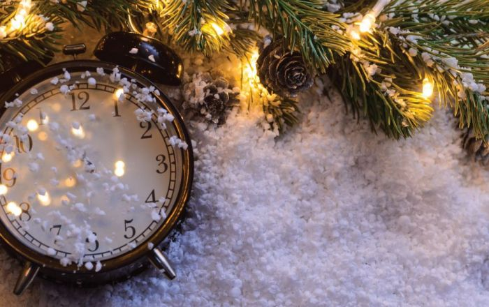 Clock on snow with pine cones