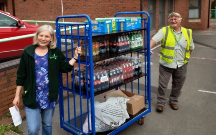 Two people moving a trolley with drinks on.