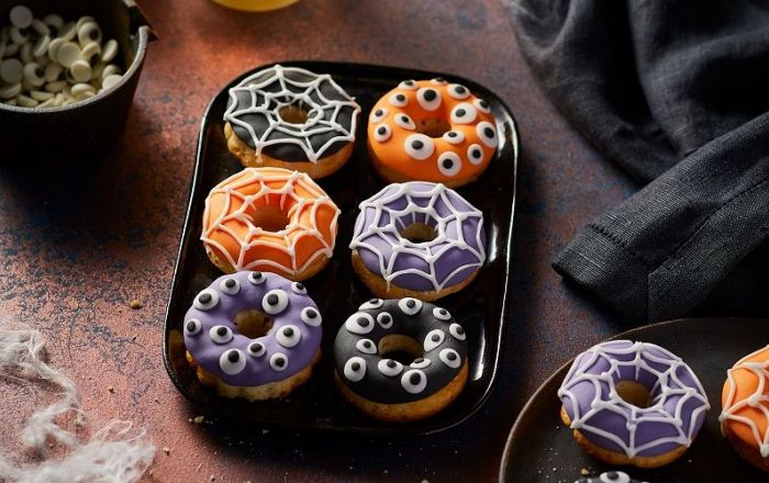 Colourful doughnuts decorated with icing in the shape of eyeballs and spider webs.