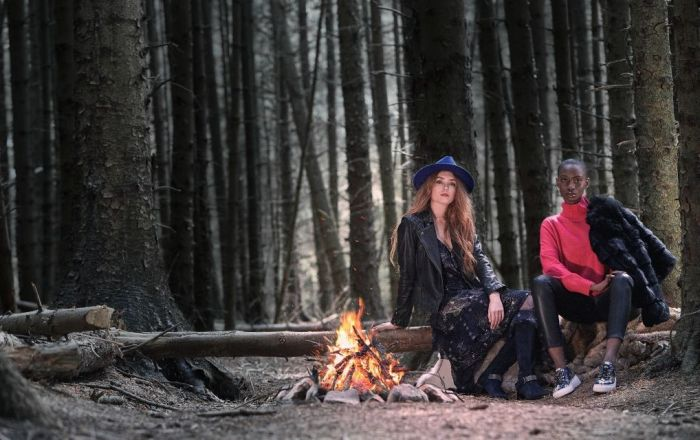 Two women sitting on a log next to a fire weaing dune shoes