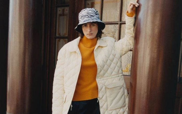 A woman wearing a padded white coat and a bucket hat.