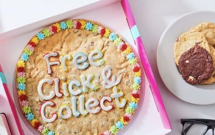 """""""Free Click and Collect"""" written in frosting on a large cookie in a box on a table next to a plate of cookies and 3 succulent plants"""