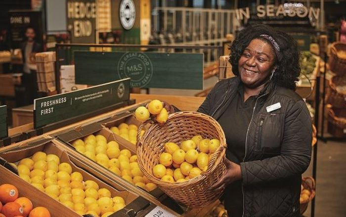 A smiling woman holding a basket of lemons.