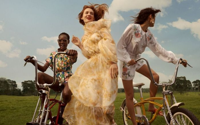 Three women wearing summer River Island clothing, two are riding 'chopper' style bikes and the central woman is running.