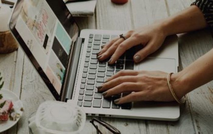 hands on a laptop on a wooden table