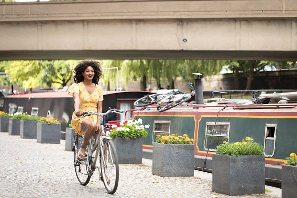 A woman riding a bike alongside a canal with barges.