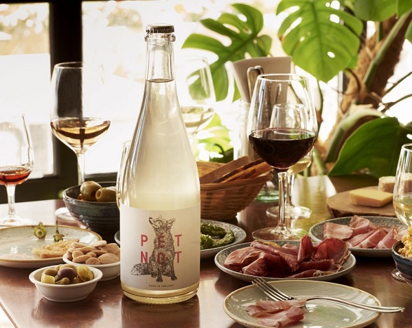 Wine bottle and glasses with various tapas style food surrounding them on a table.