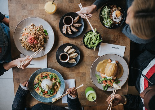 An aerial image of a table of wagamama food and people eating it with chopsticks.