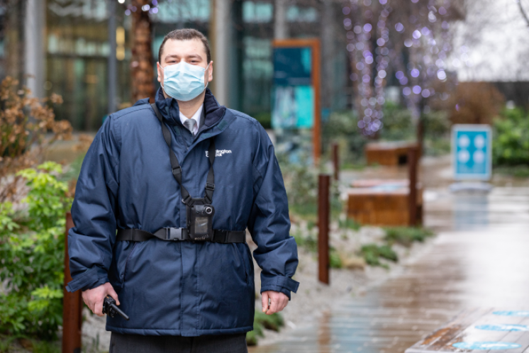 A man stood in an external area of Paddington wearing a facemask.