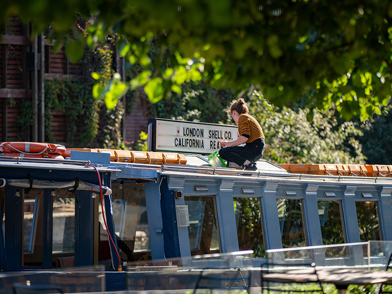 Woman cleaning the London Shell Co sign on top of a barge in the paddington central canal