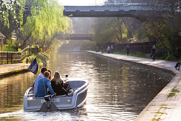 A Go Boats on the Regents Canal with a group of people riding in it