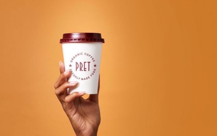 A hand holding a Pret coffee cup