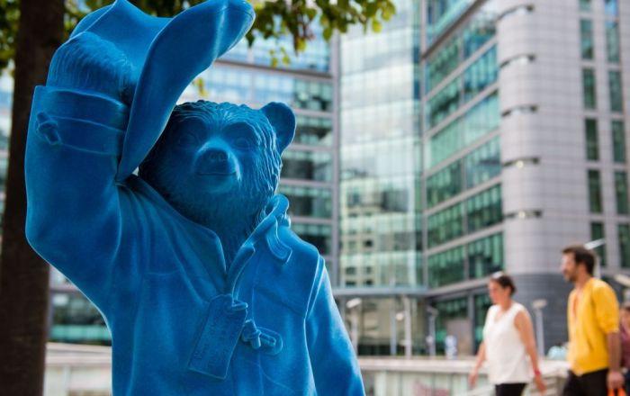 Blue Paddington Bear at Paddington Central with a couple walking past