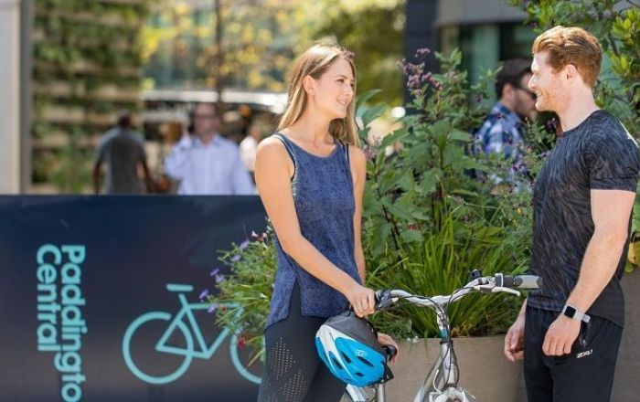 Woman and man talking while she holds her bike and helmet in front of a Paddington Central sign for bike racks