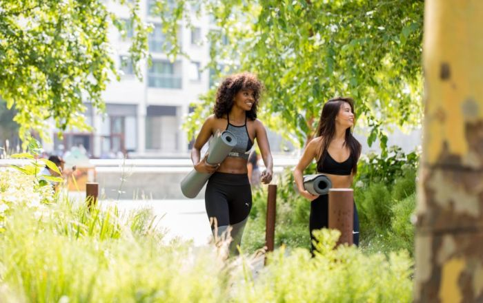 two women with yoga matts walking through trees and green area
