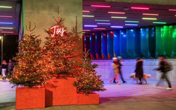 Christmas trees with a Joy neon sign
