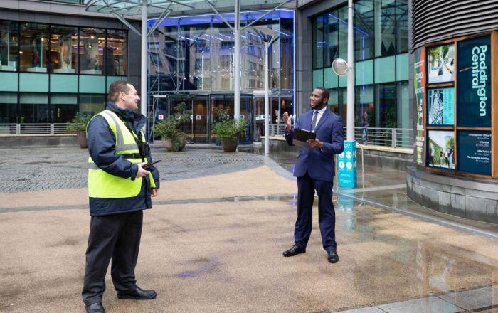 Two men standing outside Paddington Central, one holding a radio and wearing a high vis vest and another holding a clipboard.