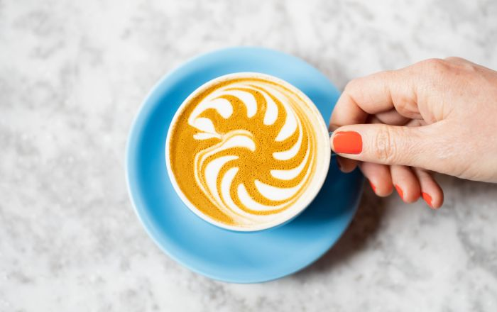 a hand wearing red polish holding a blue coffee cup with latte inside