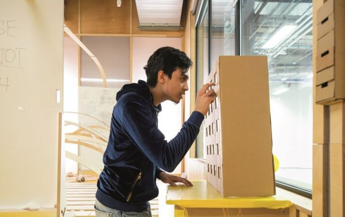 A person looking at a model building.