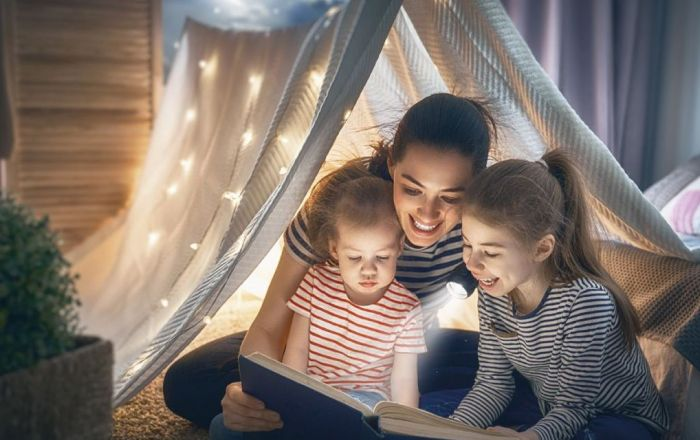 Three people under a blanket reading.