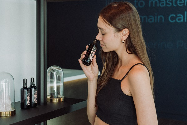 A woman smells a bottle of some kind of cosmetics.