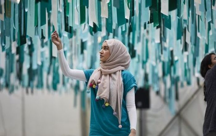 A woan wearing a head covering reaches up to a art piece which look like blue and white bunting.